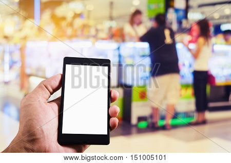 Hand man holding smart phone white screen on blurred shopping mall or blurred shopping store and department store vintage style