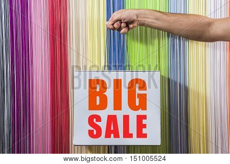detail of human hands, to hold, to shop, with a white bag, isolated on background colored blinds. With a big sale sign