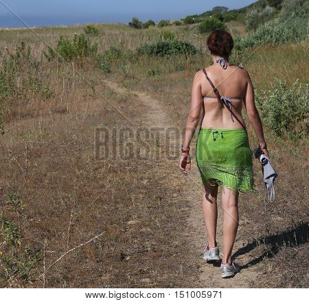 young girl keeps fit by walking with your bathing suit on the path next to the beach in summer