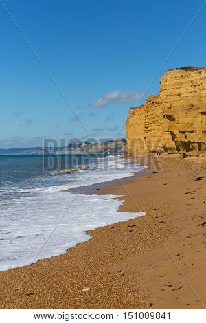 Jurassic coast beach with sandstone cliffs and white waves Burton Bradstock Dorset England UK in summer with blue sea and sky