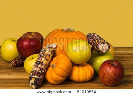 Pumpkin, green and red apples Gourds and corn on a hardwood cutting board