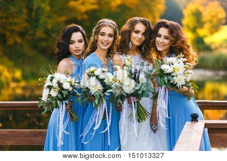 Bride with bridesmaids in the park on the wedding day