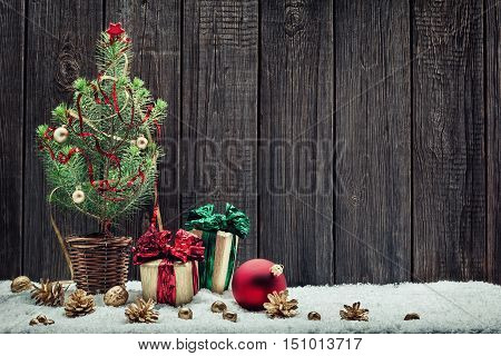 Christmas background with young Christmas tree and small gift boxes