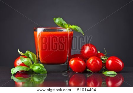 Tomato Juice With Tomatoes And Green Basil On Black Table