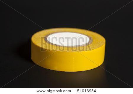 Roll of sticky insulating Scotch tape on black background