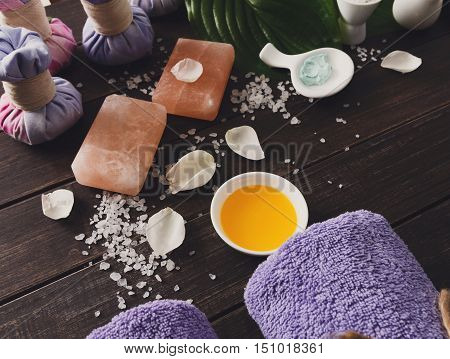 Spa treatment tools and aromatherapy concept background. Zen stones, aroma salt, spices, herbal balls, oil and soap, burning candle and details of wellness body care and alternative indian medicine.