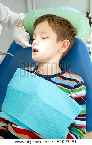 Overview of dental caries prevention. Boy at the dentist chair during a dental procedure. Little boy having his teeth examined by a dentist