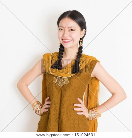 Portrait of beautiful mixed race Indian Chinese girl in traditional Punjabi dress smiling, standing on plain white background.