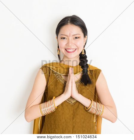 Portrait of young mixed race Indian Chinese girl in traditional punjabi dress with greeting pose, standing on plain white background.