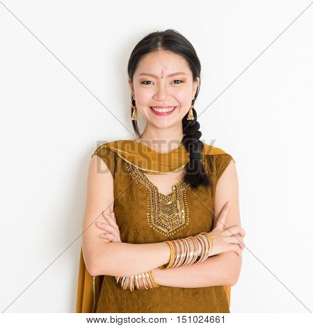 Portrait of arms crossed mixed race Indian Chinese female in traditional Punjabi dress smiling, standing on plain white background.