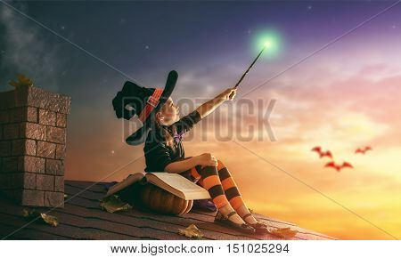 Happy Halloween! Cute cheerful little witch with a magic wand and book of spells. Beautiful child girl in witch costume sitting on the roof, conjuring and laughing.