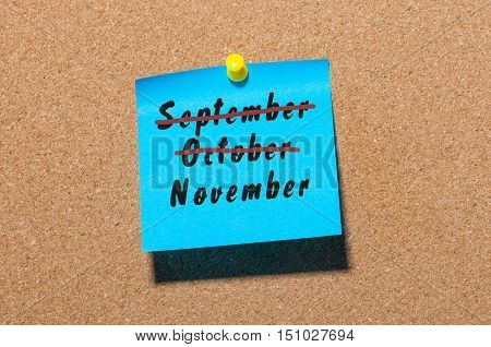 November beginning and September, October end concept written at paper pinned to cork notice board. Office, business background.