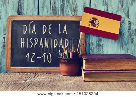 a chalkboard with the text Dia de la Hispanidad, the name for Hispanic Heritage Day in Spanish, observed on October 12, a pot with pencils, some olds books and the flag of Spain, on a wooden desk