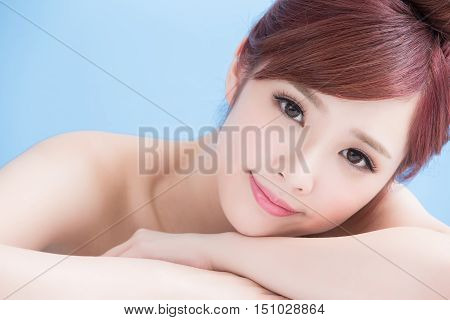 charming woman face smile to you close up while lying isolated on blue background asian girl