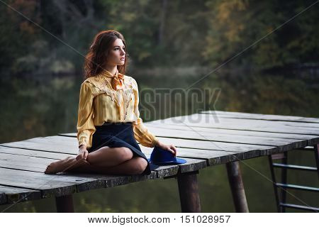 Dreaming girl with curly hair sitting on wooden bridge forest and river on background. Beautiful woman sitting by the lake. Sad girl sitting on bridge. Lonely woman sitting on a wooden bridge. Portrait of young woman on autumn background