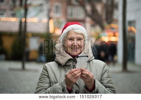 Elderly Woman At Chrismas Market With Smartphone