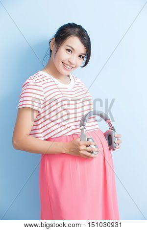 pregnant woman take earphone and smile isolated on bluebackground asian