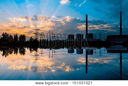 Coal-fired power plant at sunset and reflection in water