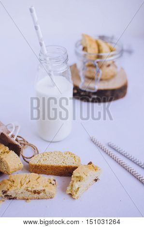 Homemade raisins cookies with bottle of milk on white baclground. Freshly baked raisin cookie. Healthy breakfast raisins cookies and milk. Tasty cookies for an afternoon snack. Selective Focus.