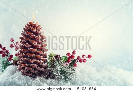 Christmas candle in shape pine cone on the snow background