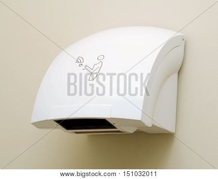 White automatic hand dryer in public wc. Toilet appliance.