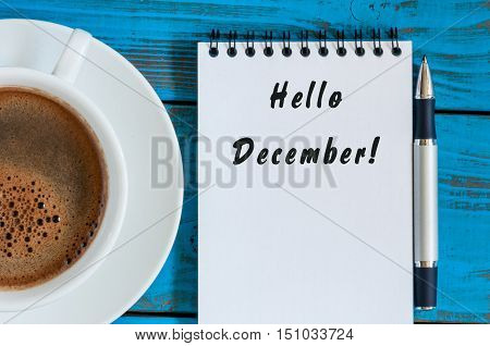 Hello December written on paper near morning coffee cup at manager or freelancer workplace. Eve, Christmas and New year time concept.