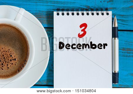 December 3rd. Day 3 of month, calendar on informal workplace background with coffee cup. Top view. Winter time. Empty space for text.