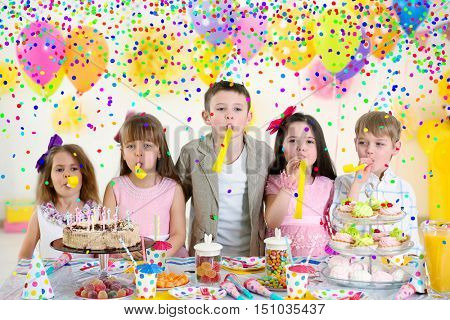 Happy group of children with yellow noise makers having fun at birthday party