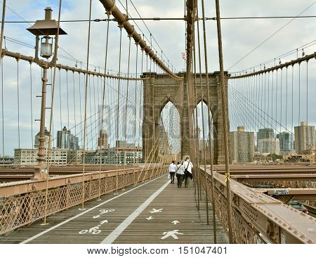 NEW YORK CITY - OCTOBER 15 2014: People walk on Brooklyn Bridge. Brooklyn Bridge connects boroughs of Manhattan and Brooklyn over East River