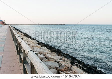 Seascape from promenade before sunset. Seawall on background