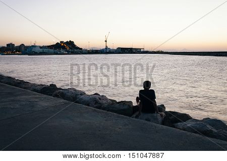 Young man looking at cityscape from promenade across the bay at night short after sunset