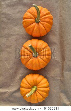 Three orange pumpkins Jack be little on paper background