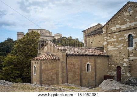 View of the back of the San Leo Church (Italy, Emilia Romagna, at the borders between Marche and Tuscany); in the background: the fortified walls of the Castle of San Leo, at the top of the appenninics hills.