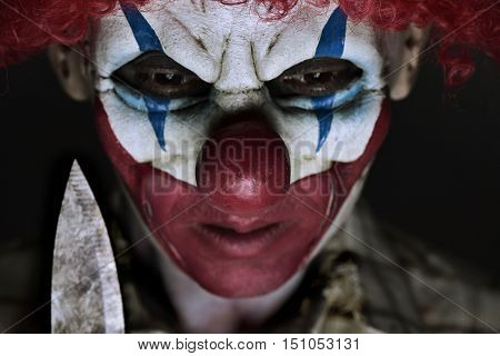 closeup of a scary evil clown wearing a ragged shirt, holding a big knife next to his face