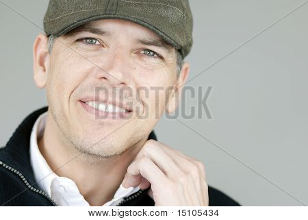 Smiling Man In Newsboy Hat Adjusts Collar