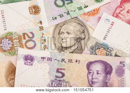 Ten dollar bill surrounded by Chinese Yuan