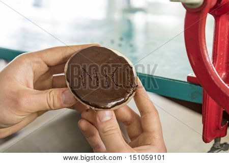 Boy holding a chocolate biscuit labelled Nice with small pinpoint pricks in a conceptual food image