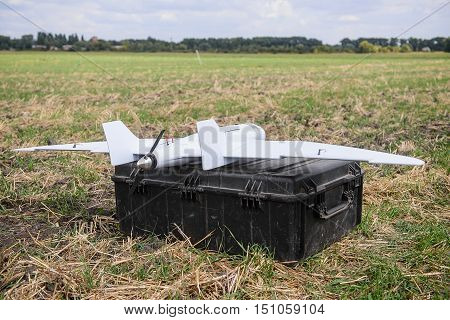 Small reconnaissance army aircraft on military box in open field before launching