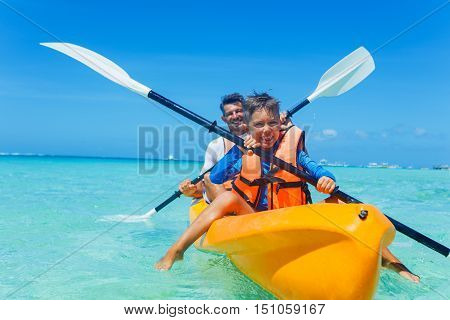 Father with his son kayaking at tropical ocean