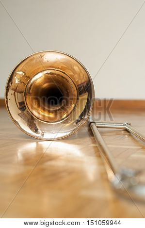 Trombone bell on brown wooden parquet bell detail selective focus