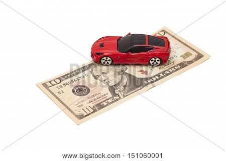 Red toy car on ten dollar banknote isolated on white background.