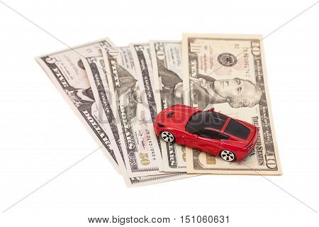 Red toy car on ten dollar banknotes isolated on white background