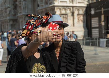 MILAN ITALY - SEPTEMBER 25 2016: Fashionable women pose outside Stella Jean fashion show building during Milan Women Fashion Week SS17.