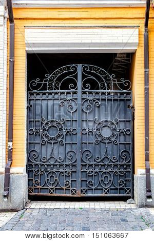 Curved pattern design on black metal vintage door. Iron gates at Vozdvizhenka street Kiev Ukraine