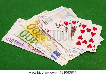 Royal flush hearts and euro money on green felt