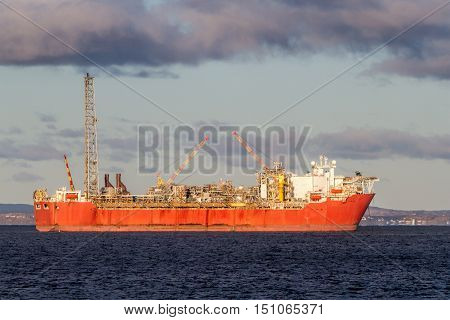 FPSO oil production vessel moored in a bay.