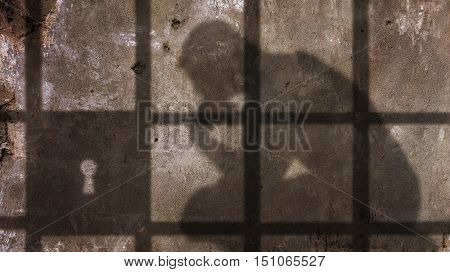Thinking man Shadow Under Jail Bars. Concrete Wall.