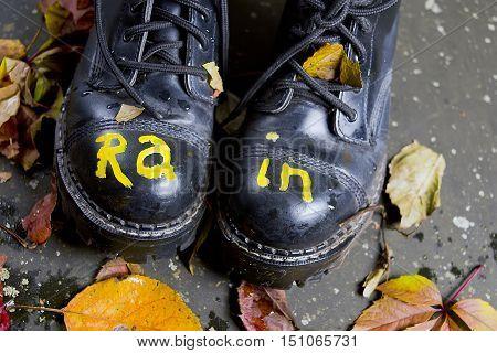 Black shoes with writing Rain walking on an autumn day studio closeup
