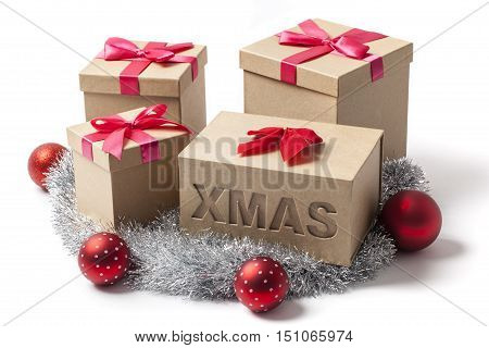 Several Christmas gift boxes tree balls and tinsel garland isolated on white.