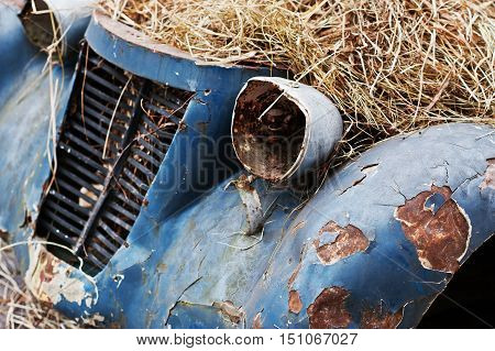 Old Abandoned Car With Hay On Engine